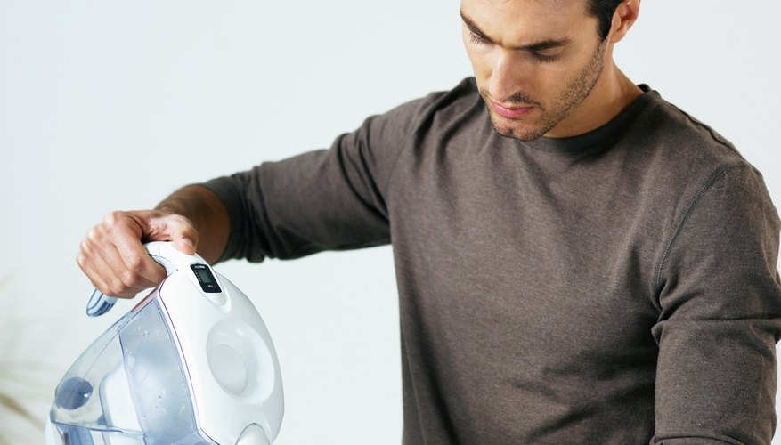 Man in kitchen pouring glass of water from jug