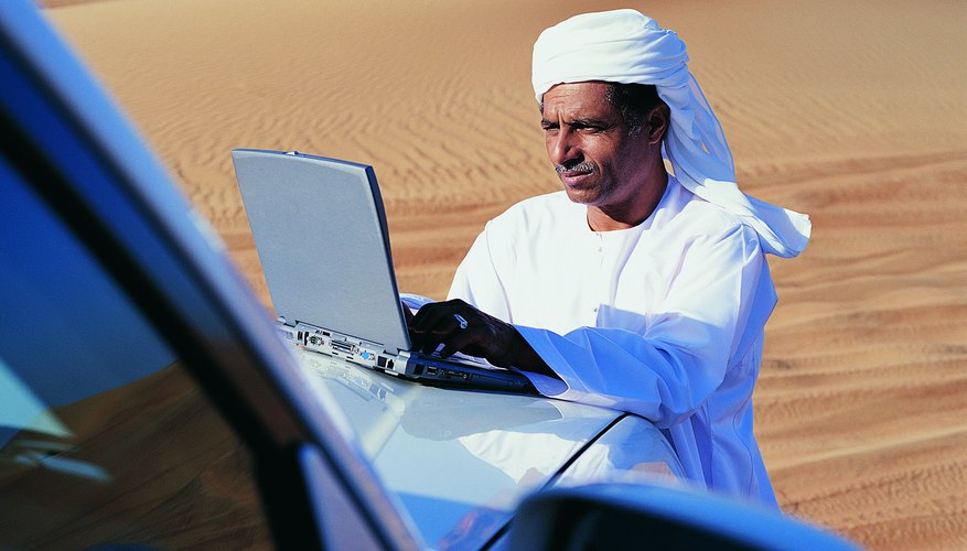 Man in Traditional Middle Eastern Dress Using a Laptop on a Car Bonnet in the Desert