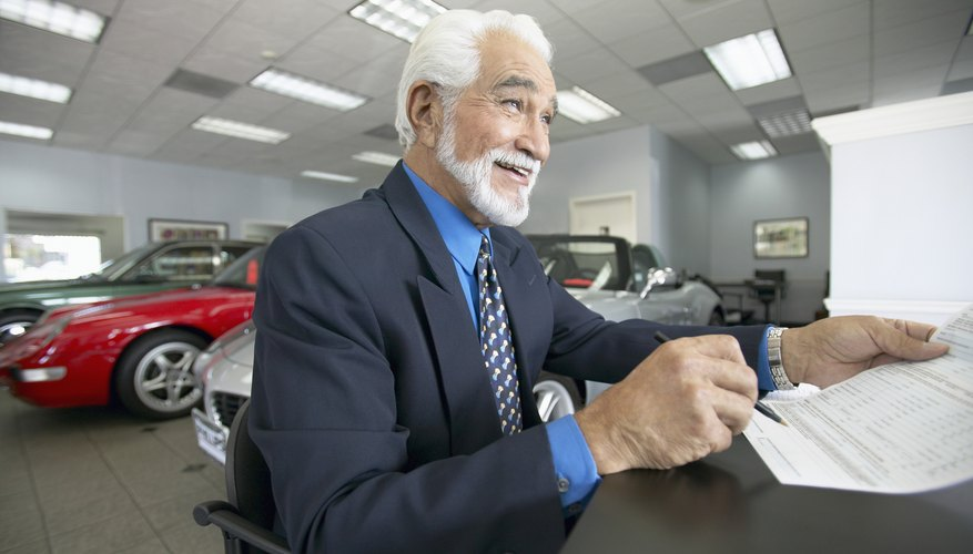 Senior Salesman Sits at a Table in a Car Showroom, Holding a Document
