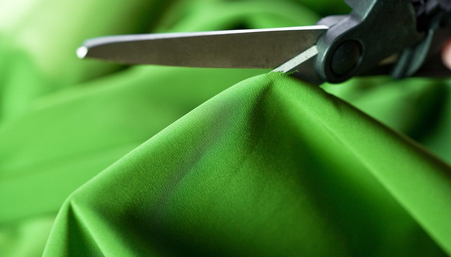 Scissors cutting green fabric