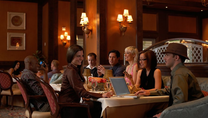 Group of people sitting at restaurant table, man using laptop, smiling