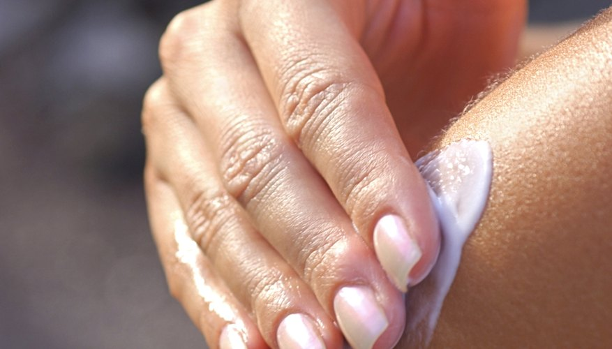 Girl putting lotion on skin
