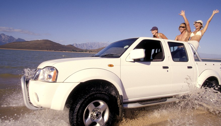 Woman in truck driving across seashore