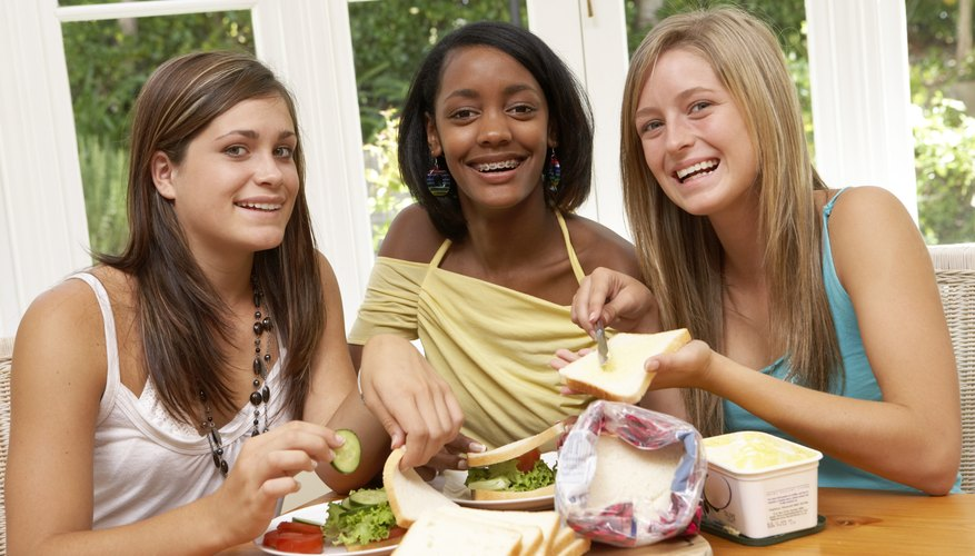 Three girls making sandwiches together.
