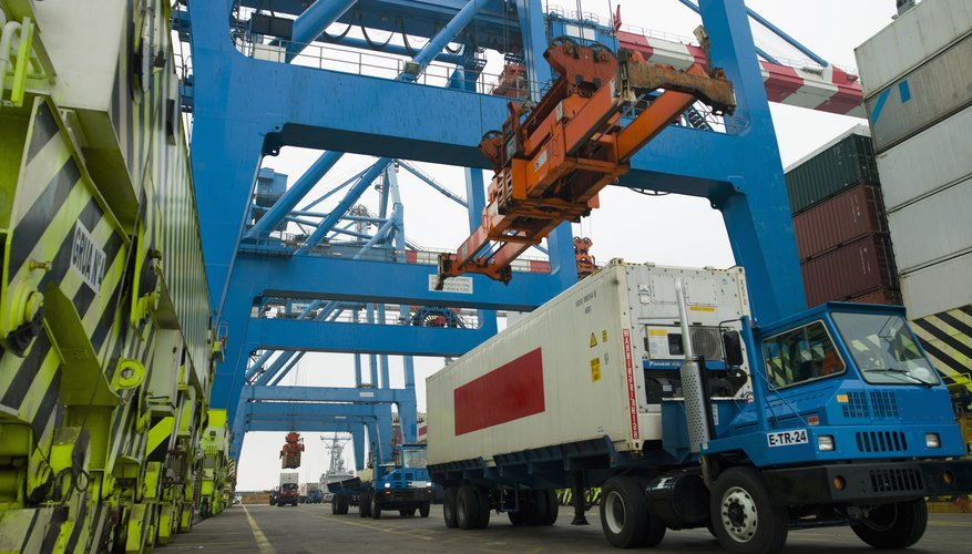 Container being loaded onto truck in shipping yard