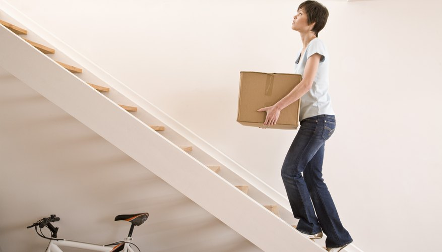Woman carrying box up stairs