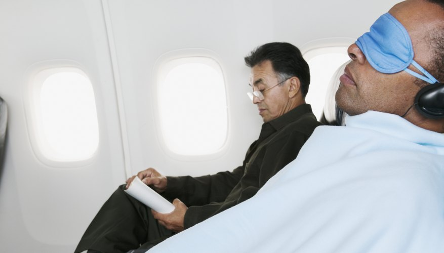 Two men are flying on a commercial plane.