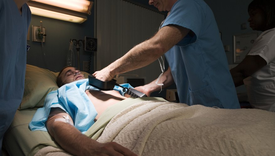 Doctors defibrillating patient in hospital bed