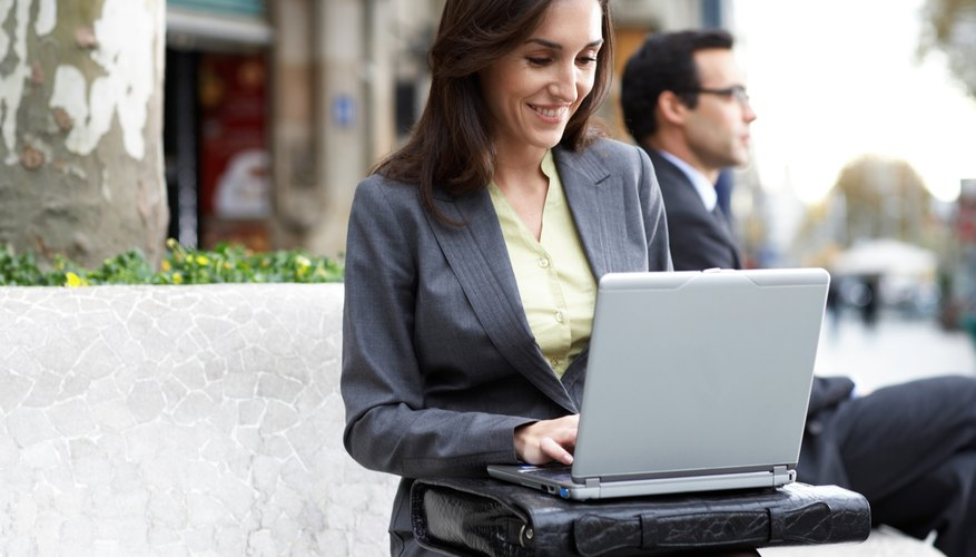 Businesswoman using laptop outdoors, smiling