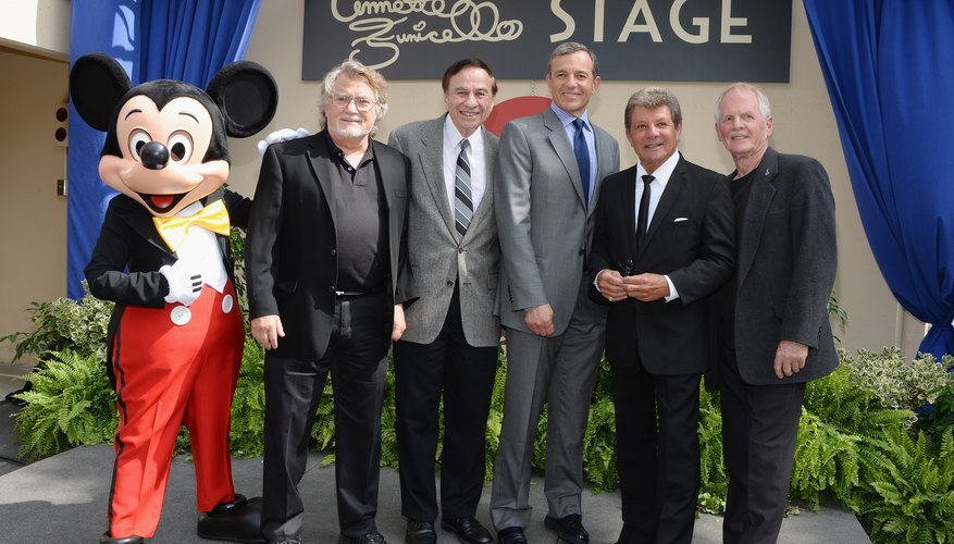 The CEO of the Disney Company posing with team members and Mickey Mouse at an event.