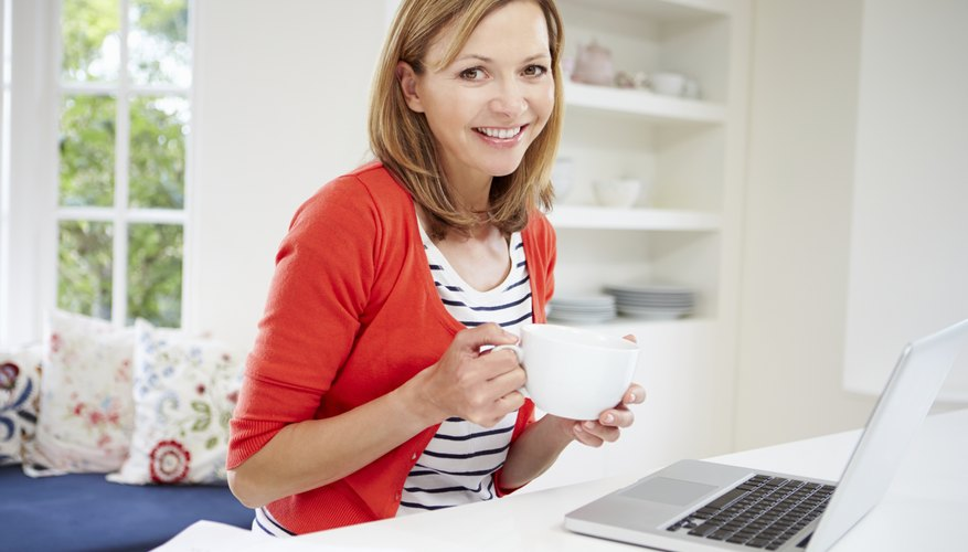 Woman Working From Home Using Laptop In Kitchen