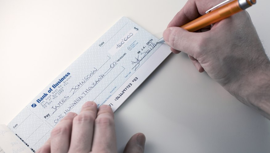 Hands writing on a cheque