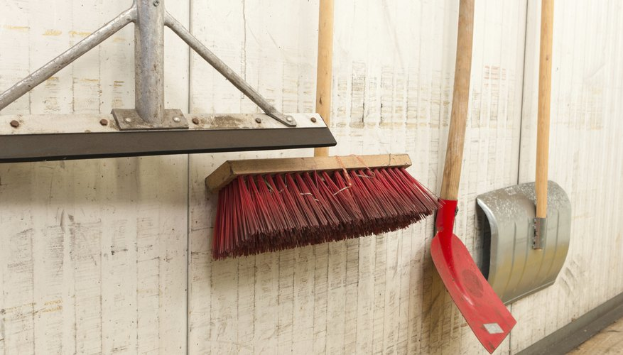 An assortment of brooms and shovels haning on a wall.