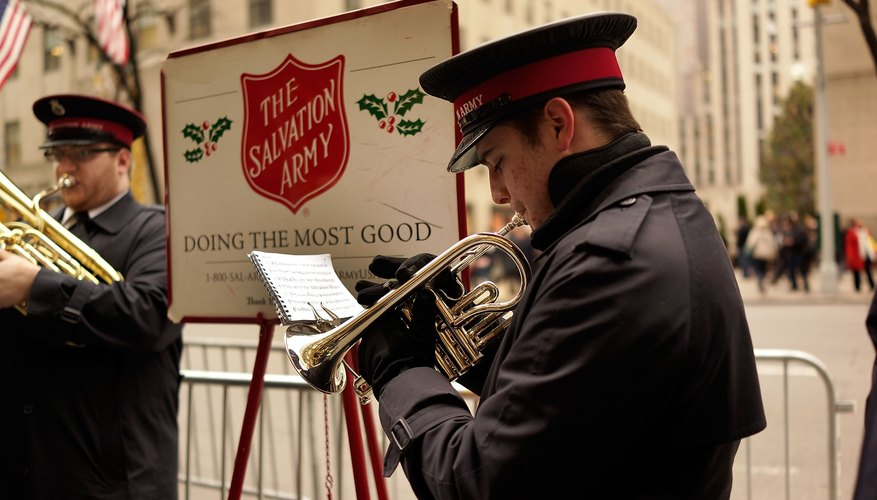 Man playing trumpet in front of The Salvation Army sign.
