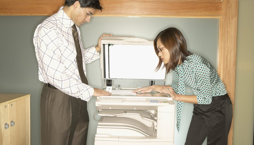 Businessman and a businesswoman using a photocopier