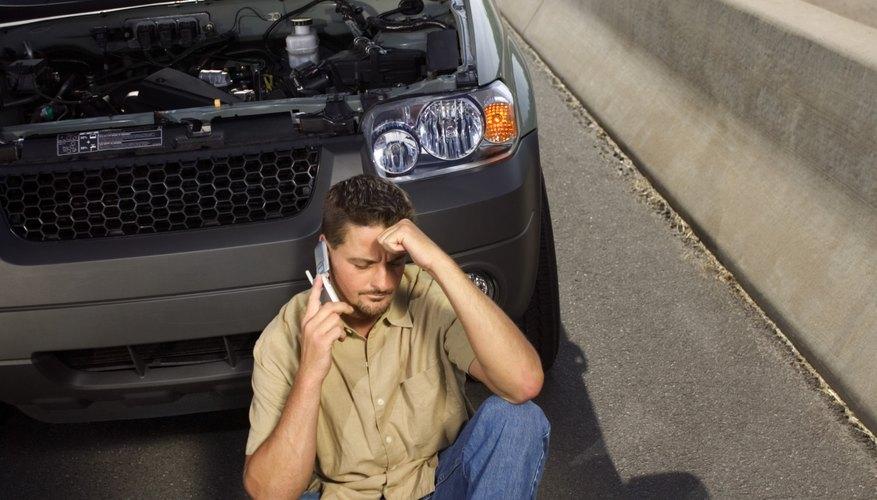 Man sitting next to broken down car on highway
