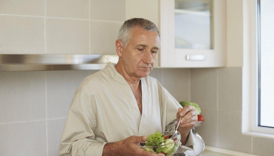 An older man eats a small salad.