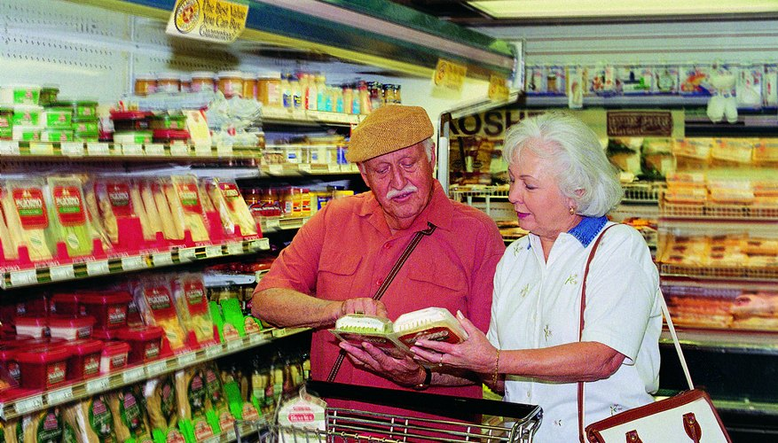 Elderly couple shopping together with book