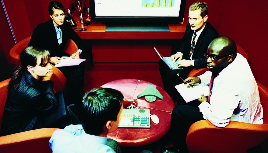 Business Executives in a Meeting With a Plasma Screen Showing Graphs