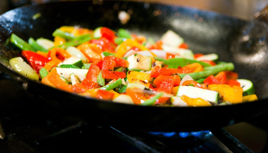 Vegetables cook on a gas stove.