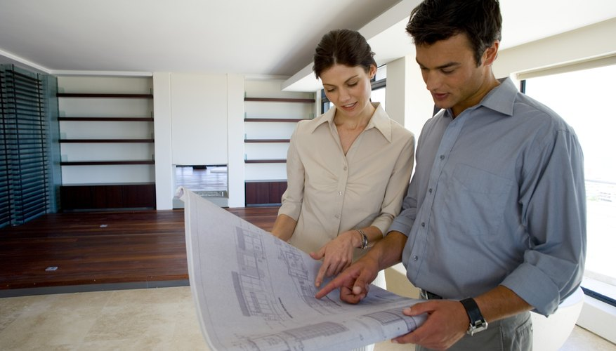 Couple discussing home remodel while looking at blueprints.