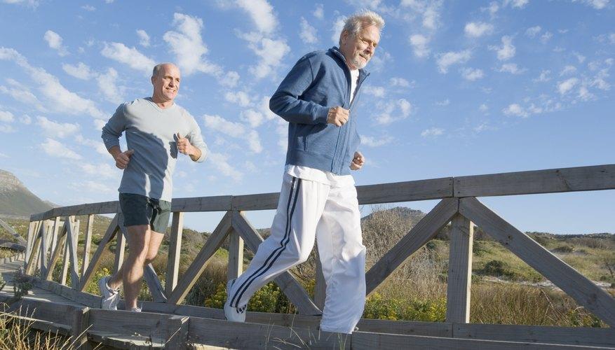 Two older men jog across a bridge.