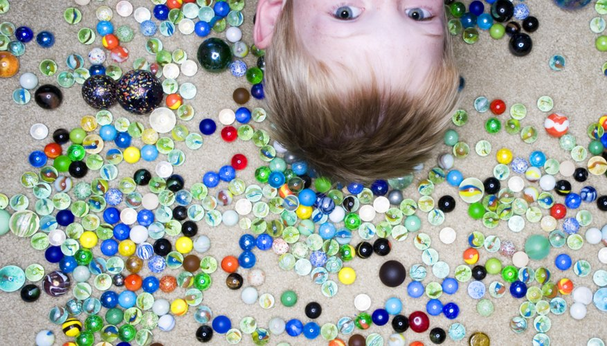 Young boy surrounded by marbles