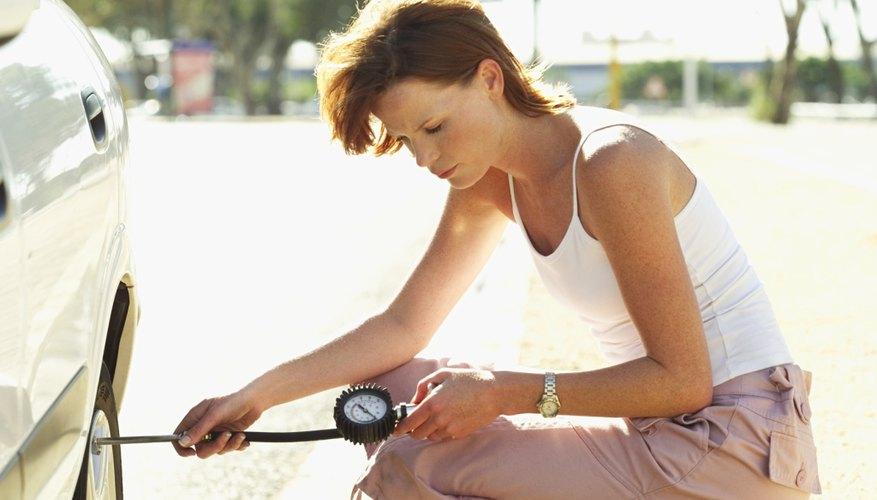 woman checking air pressure of a car tire