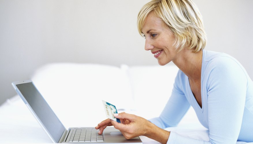 Woman holding up a credit card and working on a laptop.