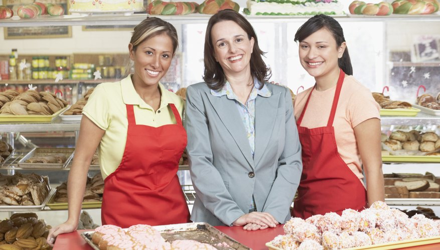 Portrait of a businesswoman smiling with two female bakers in a bakery