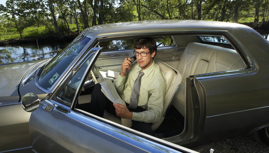Businessman in car using cell phone, portrait