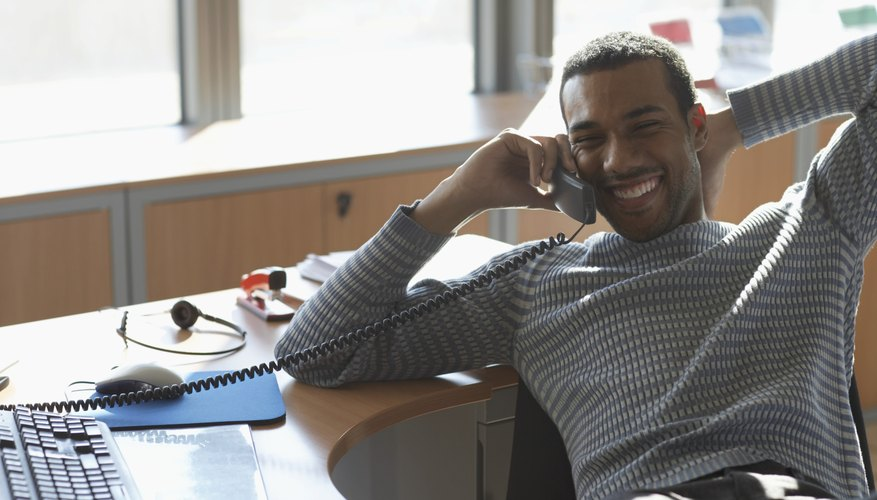 Businessman at desk using telephone, smiling