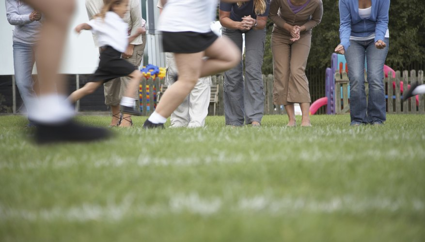 Parents cheer for young runners at a track and field event.