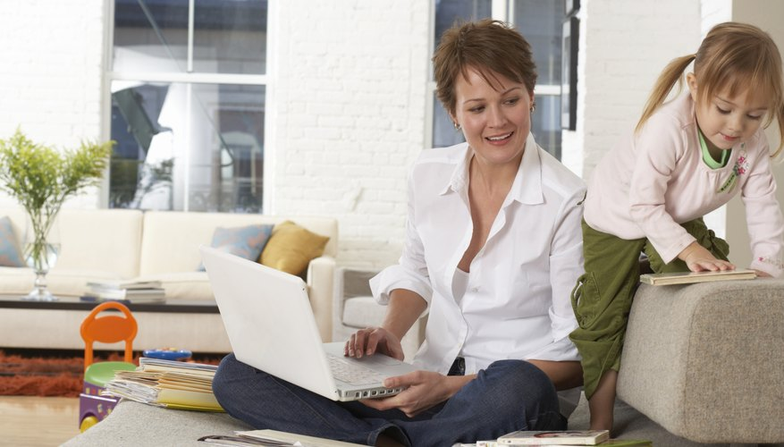 Woman using laptop on sofa by daughter (2-4), smiling