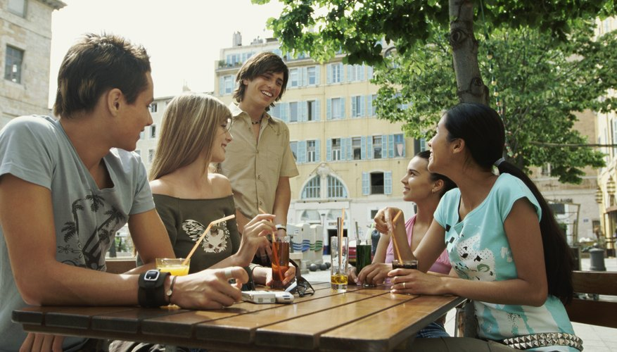 A group of young adults meet at a table outside.