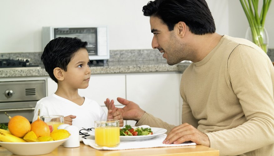 Father talking to his son at the breakfast table.