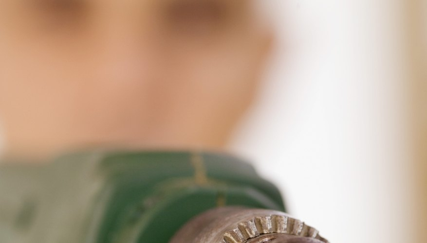Man using electric drill, close-up, selective focus, focus on drill