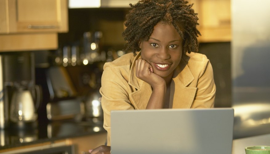Young African woman in kitchen with laptop