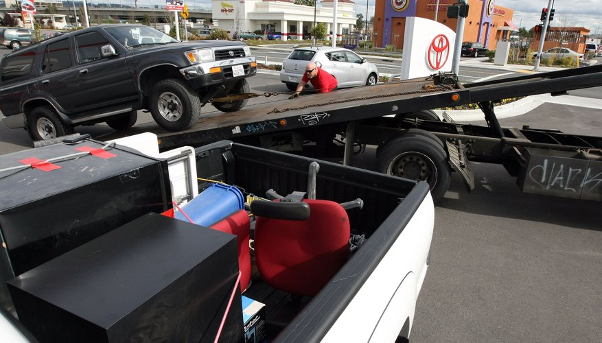 A tow truck driver loads a Toyota 4 Runner onto his truck in Oakland California.