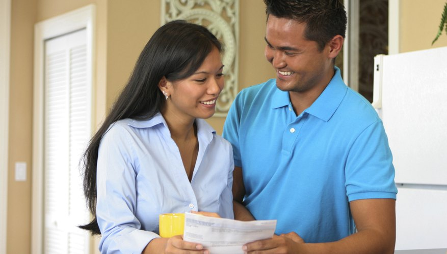 Young couple holding a bill smiling