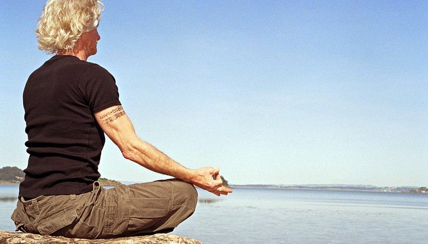 A woman meditates near the ocean.
