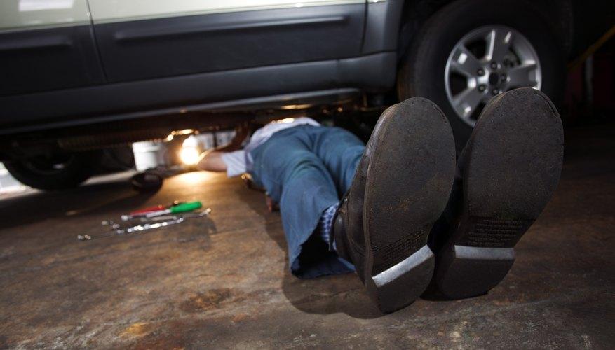 Feet of mechanic working under SUV