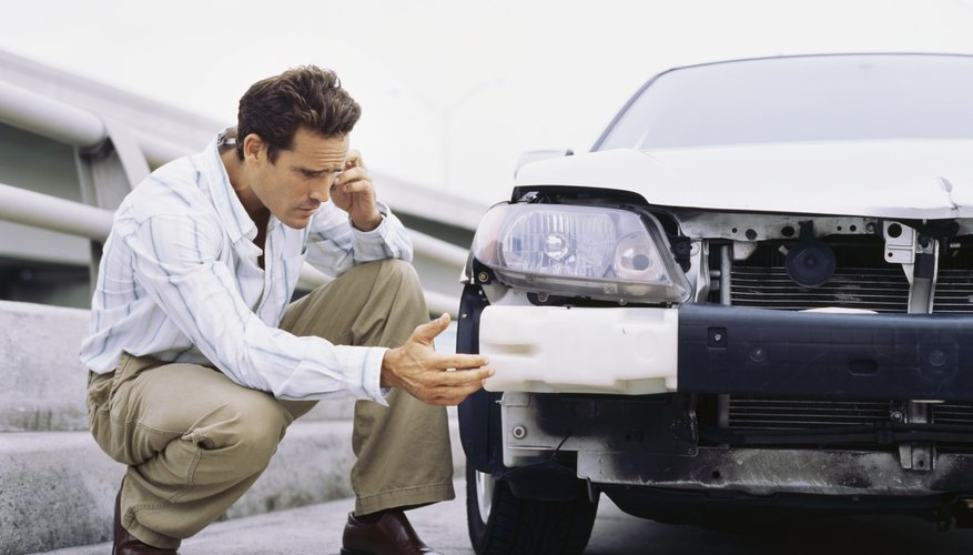 Mid adult man examining a car involved in an accident and talking on a mobile phone