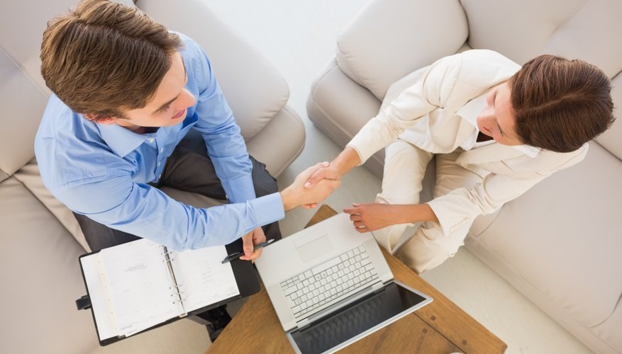 Business team working together on the couch shaking hands