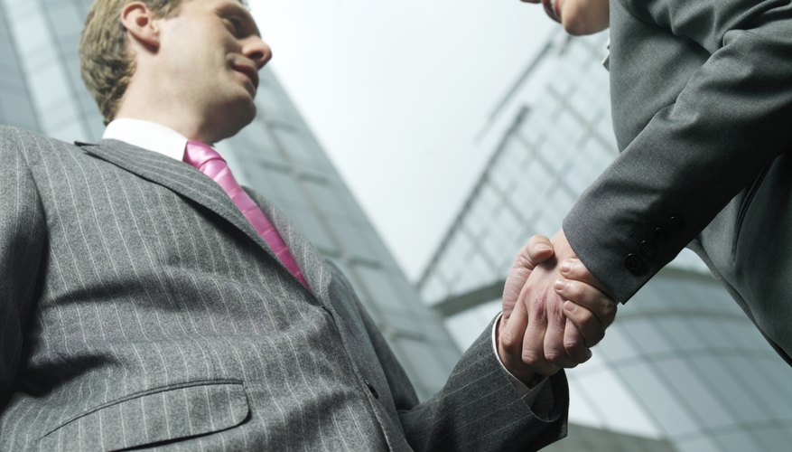 Two businessmen shaking hands outside office building, low angle view