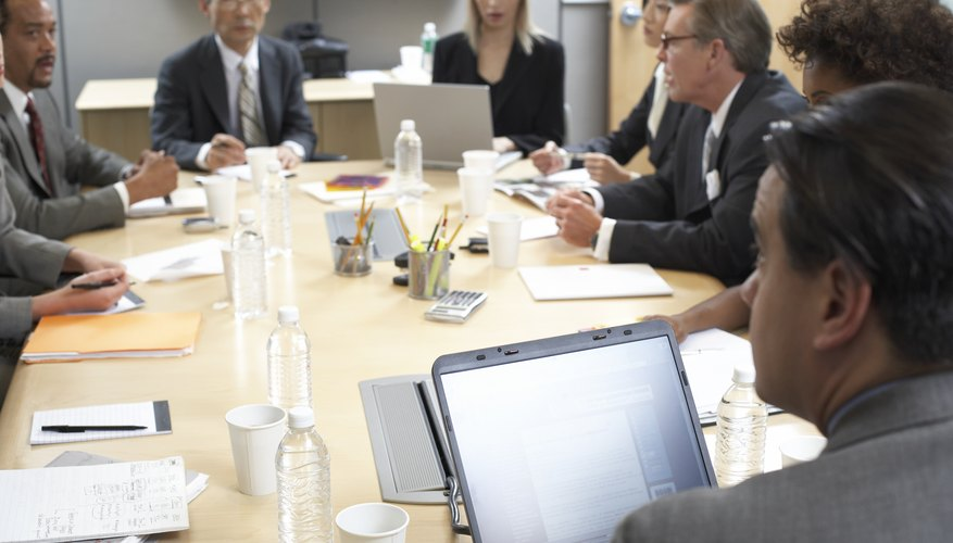 Businessmen and women around conference table in meeting