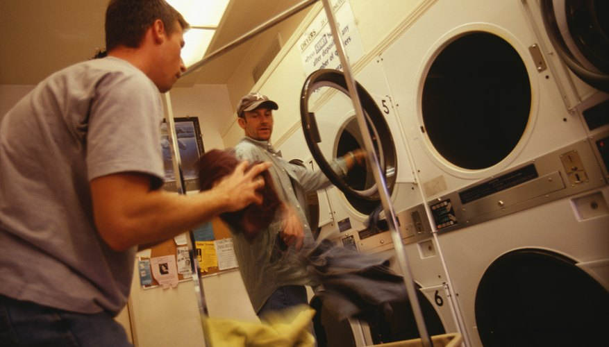 Gay couple putting clothes into dryer