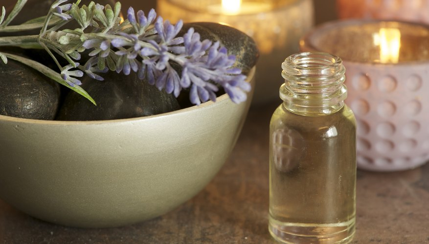 A bottle of lavender oil next to candles and a lavender leaf