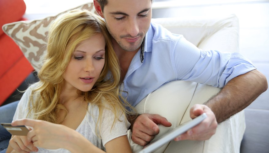 Image of a couple at home shopping on their tablet.