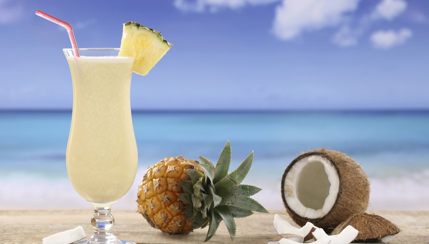 Coconut oil can dissolve in an aqueous pina colada because of the amphipathic nature of rum
